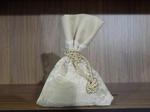 Μπομπονιέρα γάμου σε ιδιαίτερο σατέν πουγκί με λεπτομέρειες δαντέλας και δέσιμο με χρυσό κορδόνι