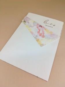 Προσκλητήριο γάμου με χρωματισμούς νερομπογιάς και χρυσοτυπία τα μονογράμματα σε ροζ χρυσό
